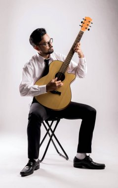 portrait of asian businessman playing guitar on chair
