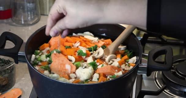 Žena sůl ve zpomaleném filmu ingredience v pánvi pro výrobu smetanové polévky stojící na plynovém sporáku. Zdravý stravovací koncept.