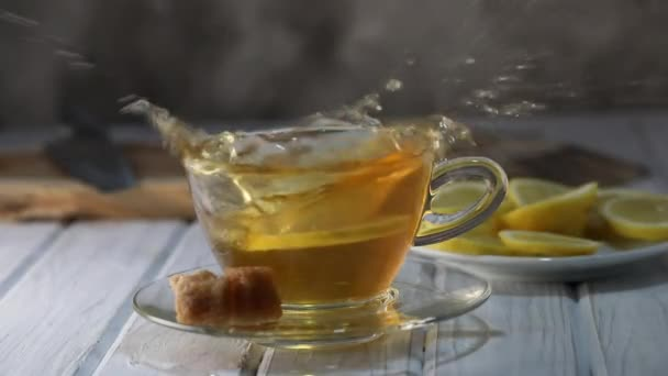 Lemon slice falls into a cup of hot tea in slow motion