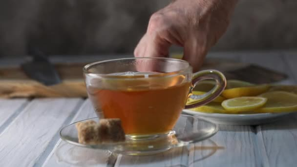 Lemon slice falls into a cup of hot tea in slow motion.
