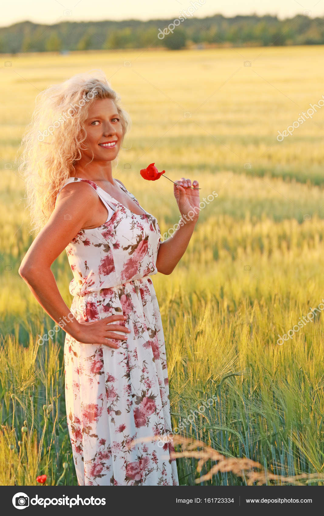 a12f3cd127c2 Happy mature woman with a long dress in summer evening in front of a corn  field — Photo by ...