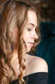 Gyönyörű nő hosszú göndör hajjal és arany ékszerekkel. pózol egy kávézóban, nagy fülbevalók, nevetés, flörtölés.