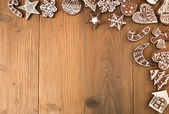 Row of Christmas gingerbread cookies on old wooden table.