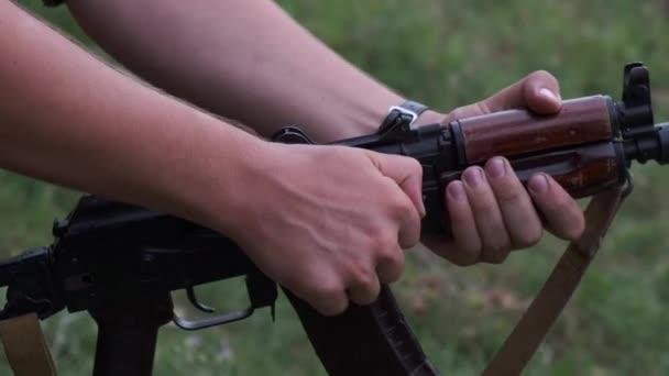 Egy álcázott férfi kezéről, aki golyókat töltött egy fegyverkamrába. Meghúzza a zárat.