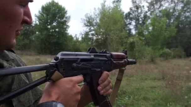 Oroszország, Maykop - 2019. augusztus 2. Egy álcázott férfi kezéről, aki golyókat töltött a lövészkamrába. Meghúzza a reteszt és tüzel az Ak-74-es katonai fegyverekkel.