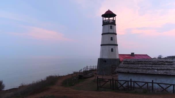 Malý bílý maják s červenou střechou a nedalekou lodí podél pobřeží ve vesnici s domy. Večerní západ slunce s růžově modrou oblohou a načechranými bílými mraky.