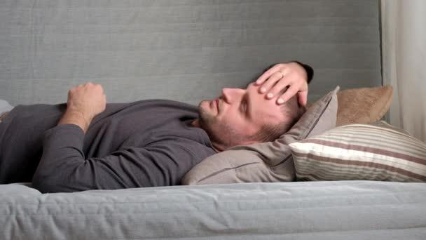 Mosolygó ember hazudik, és pihentető a kanapén, otthon a nappaliban