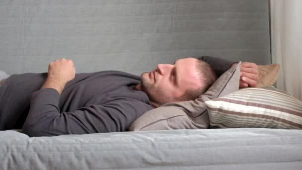 Usmívající se muž ležící a relaxaci na gauči doma v obývacím pokoji