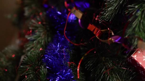 Close-up of decorated Christmas tree branches with colorful shiny tinsel garlands and colored toys. Home decoration for Christmas, New year.