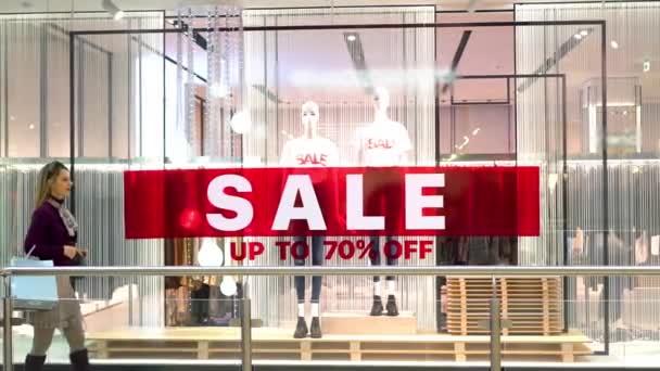 Štíhlá, elegantní Shopaholik žena chodí s nákupními taškami kolem obrovské červené prodejní cedule v okně módní butik na ulici.