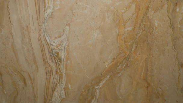 Pevný kus mramoru v béžových tónech v moderním interiéru pro interiérovou výzdobu koupelny a kuchyně, posuvný fotoaparát shora dolů.