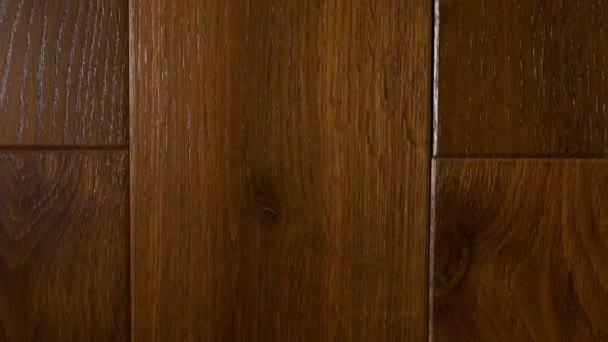 Detailní záběr dřevěných podlah z masivních dřevěných prken z tmavého moka dubu v hnědých tónech v moderním interiéru, interiérová výzdoba místnosti, parketové podlahy, masivní dřevěné podlahy.