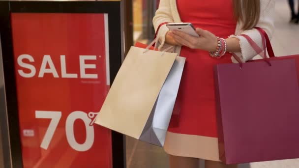 Obchodník dívka s nákupními taškami stojí vedle nápisu prodej 70% v obchodě, módní butik a pomocí smartphone mobilní telefony číselníky Sms, chaty na internetu.