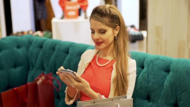 Shopaholic žena nakupující s nákupními taškami sedí na pohovce v butikovém obchodě a pomocí smartphone mobilní telefon Sms v sociálních sítích chat a usmívat, žena nakupuje on-line