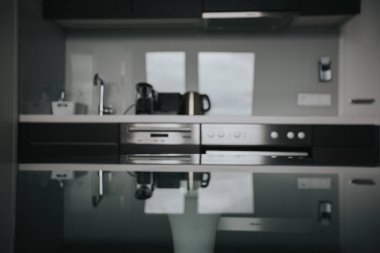 Interior of a kitchen. Focus in front on the glass table with blurred background. Natural light and desk space.