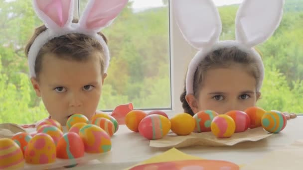 Funny boy and girl with rabbit ears on the head. Children dressed up for Happy Easter. Kids with easter eggs on the background of the window.