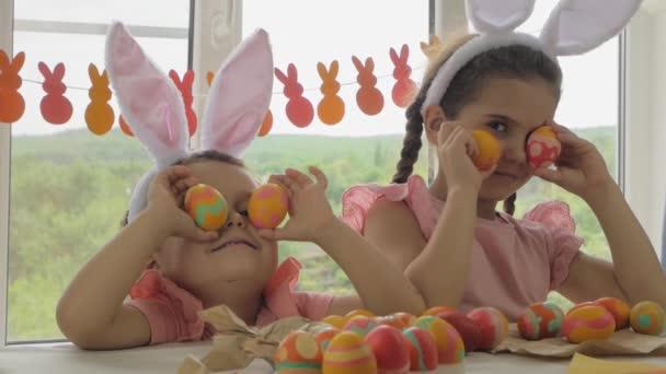Vicces fiú és lány nyúl fülekkel a fején. Gyerekek kiöltözve Boldog Húsvétot. Gyerekek húsvéti tojással a háttérben az ablak.