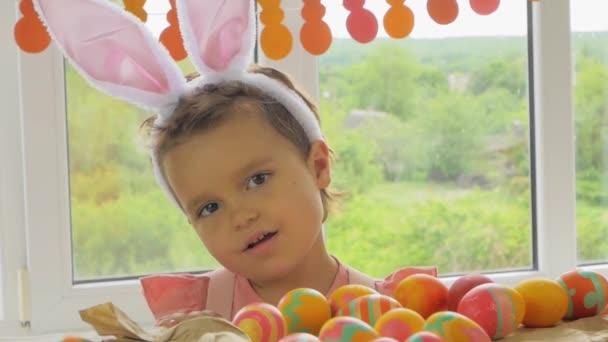Vicces baba nyuszifülekkel a fején. A fiú húsvétra öltözött. Gyerek húsvéti tojás az ablakon háttér