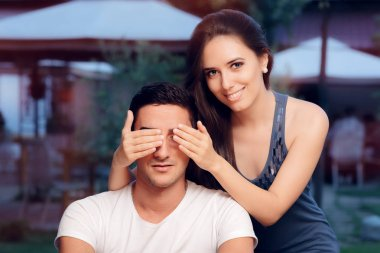 Woman Covering Mans Eyes Taking him by Surprise on a Blind Date