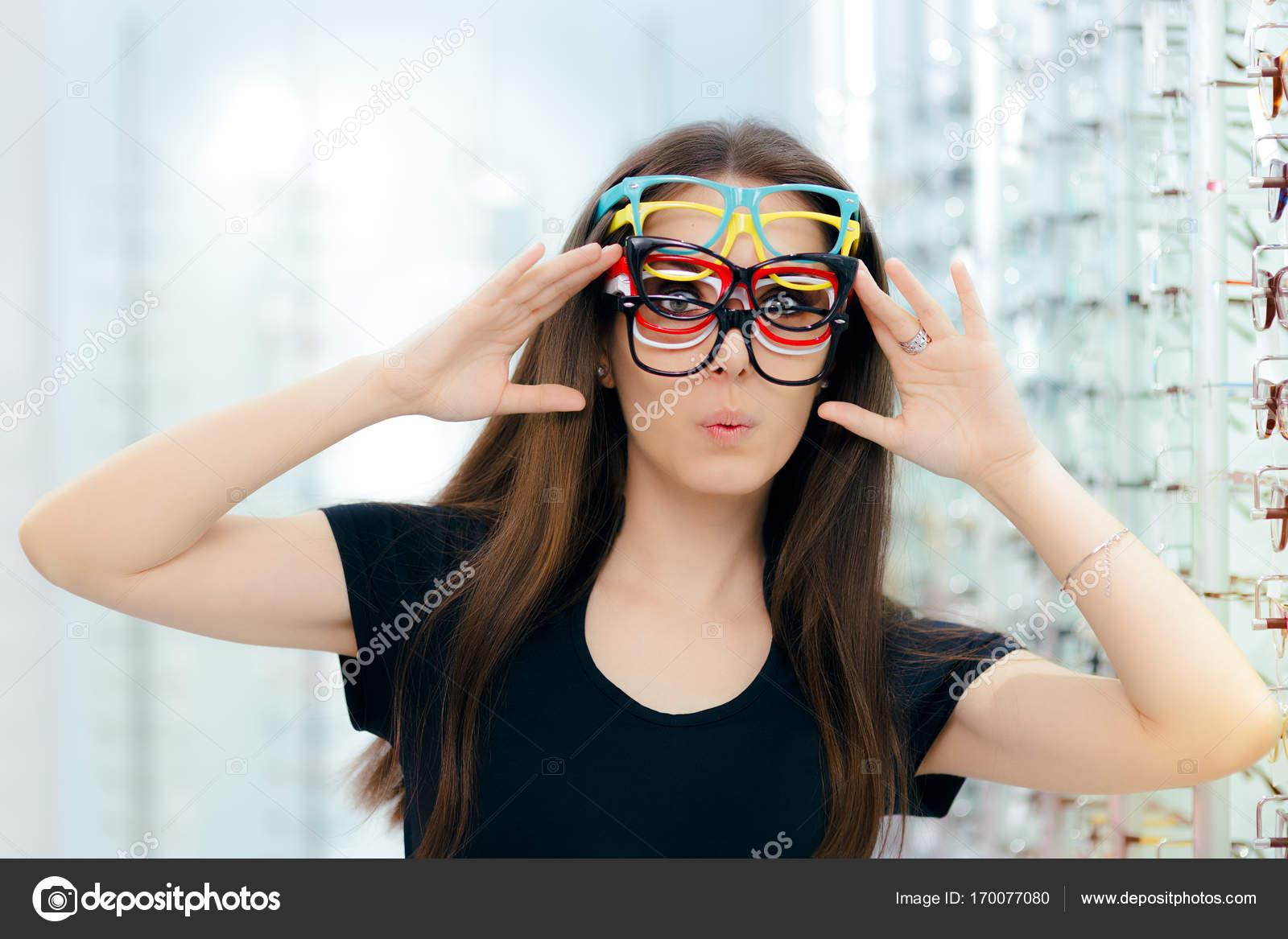 Mujer divertida tratando de muchos marcos de anteojos en óptica ...