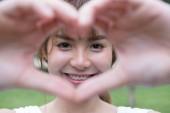 fiatal nő, ami a szív ujjai mozdulatot. Ázsiai lány