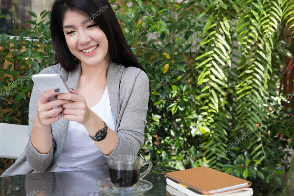 asian woman sit at outdoor cafe. young female adult use mobile p