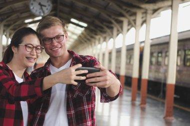 man & woman use smart phone to take selfie photo at train statio