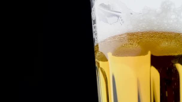 A hideg, könnyű kézműves sört pohárba öntik. Egy közeli videó fekete háttérrel. Másold a helyet. 4K UHD videó 3840x2160