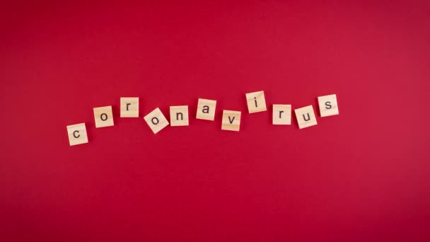 Wooden cubes with letters on a red background line up in the word Coronavirus. Stop motion video. Full HD 1920x1080
