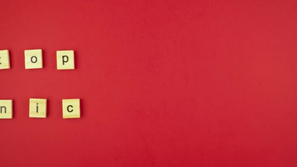 Wooden cubes with letters on a red background line up in the words Stop Panic. Stop motion video. 4K UHD 3840x2160