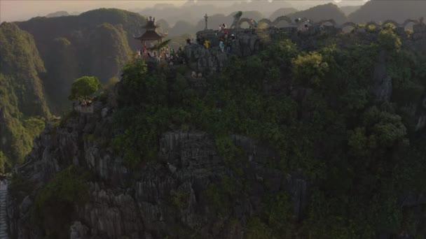 Turisté vylézt na slavný Ležící drak hora socha během krásného západu slunce v Ninh Binh provincie v severním Vietnamu