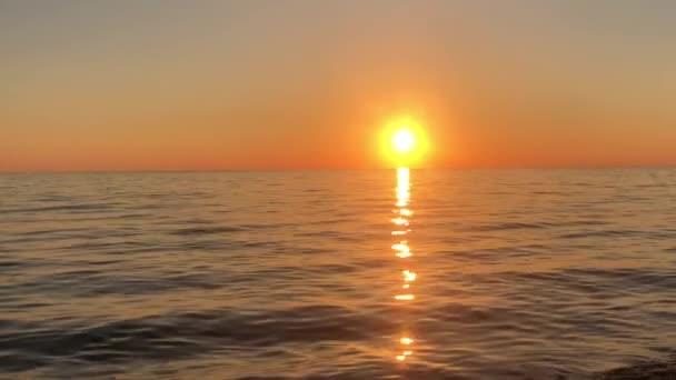 Východ slunce nad klidným mořem. Letní slunce se odráží od vody. Západ slunce nad obzorem velkého jezera. Sluneční paprsky září na vlnách oceánu.