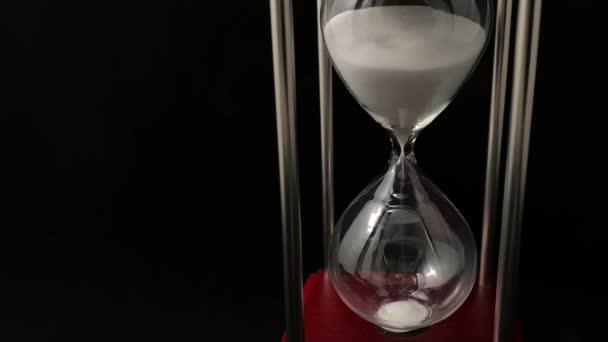 Homokóra a lelátón, fekete háttér. Üveghomokóra a táskában. Üveg időmérő. Koncepció: fogy az idő, időgazdálkodás, időérték