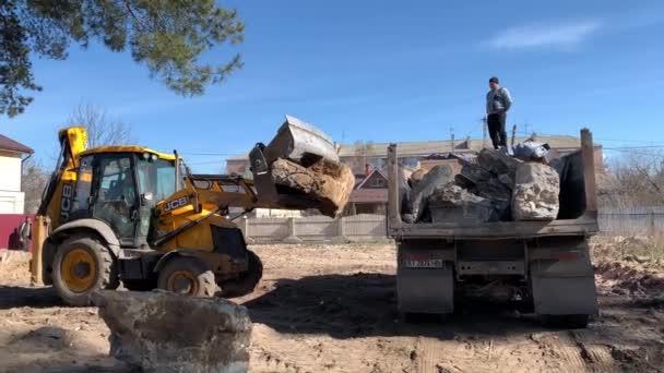 Traktor a náklaďák poblíž zničeného cihlového domu. Stavební stroje na pozadí zříceniny domu. Zbourání starého domu s bagrem. Irpin, Kyjevská oblast, 13. března. 2020