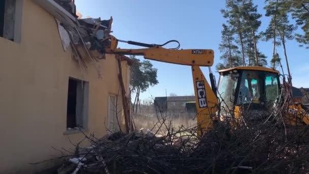 Těžké vybavení poblíž zničeného cihlového domu. Stavební stroje na pozadí zříceniny domu. Zbourání starého domu s bagrem. Irpin, Kyjevská oblast, 13. března.