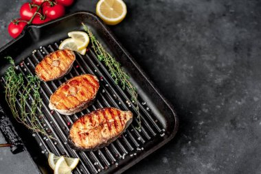 Grilled salmon steaks with on a grill pan with spices on a stone background with copy space for your background