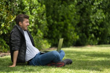 Caucasian man laughing while he is looking at his laptop. Natural Environment