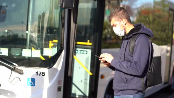 Young caucasian man wearing face mask and looking at mobile while taking the bus during pandemic covid-19. Health and care concept