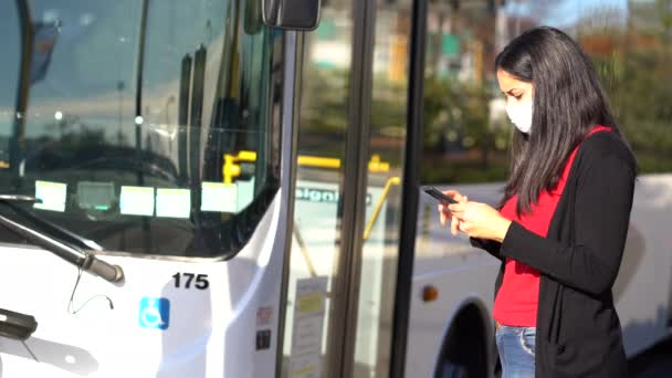 Young brunette woman wearing face mask at the bus stop while looking at her mobile. Coronavirus concept