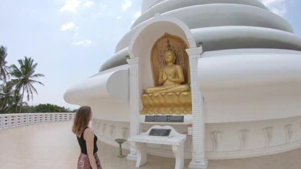 Kaukázusi lány imádkozzon Buddha előtt Srí Lankán.