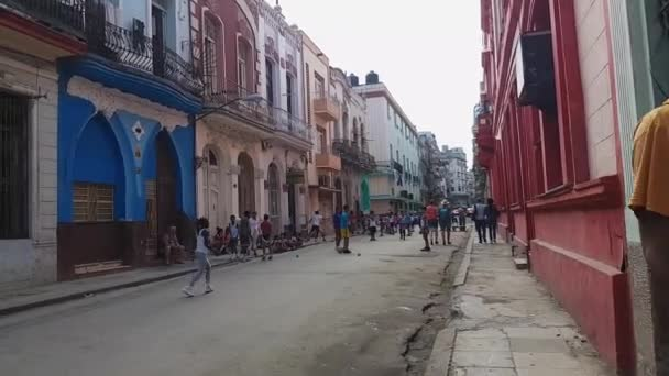 Man painting blu Cuban car, kids play foodball in alley of Havana