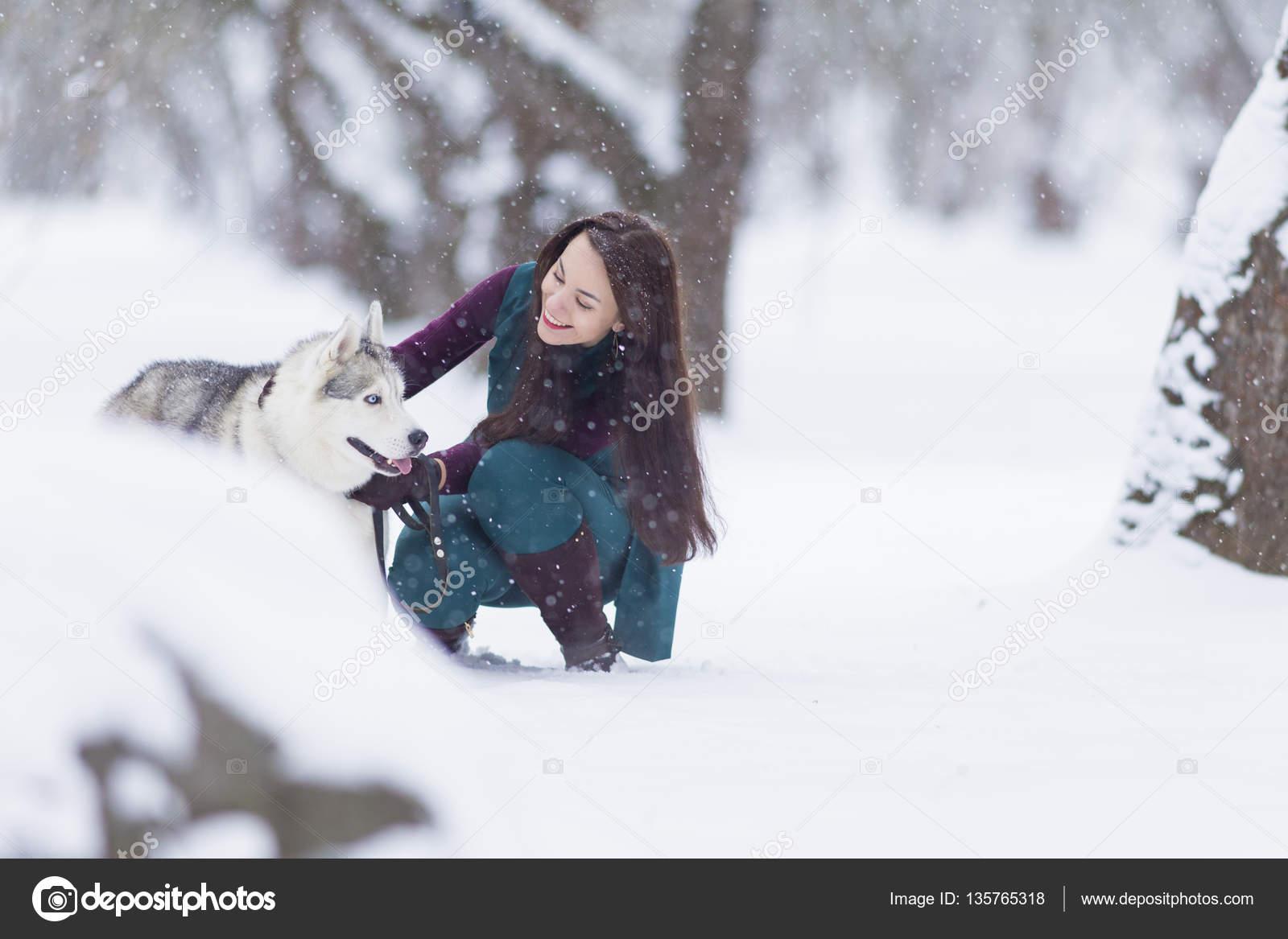 378d90a17013 Τα κατοικίδια έννοιες και ιδέες. Χαρούμενος και χαμογελαστός Καυκάσιος  μελαχρινή γυναίκα παίζει με σκυλιά Husky