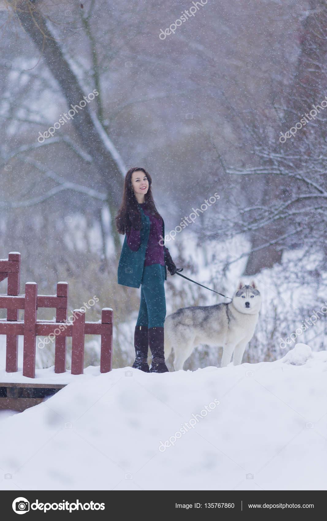 c3d75a3c906a Ζώα και κατοικίδια έννοια και οι ιδέες. Αρκετά ήσυχο Μελαχρινή καυκάσιος με  ο μεγαλόσωμος σκύλος της κατά τη διάρκεια μια βόλτα στο Winter.