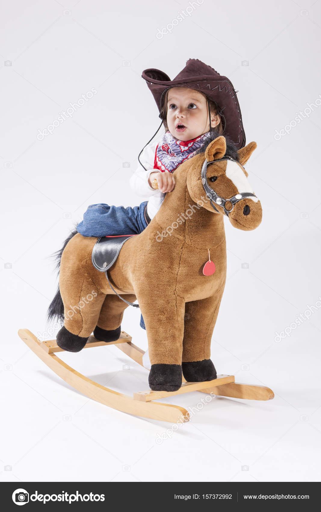 6ca2e62117 Consepts de niños. Caucásica niña posando en ropa vaquera con caballo de  juguete contra la composición de la imagen en blanco Background.