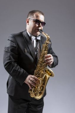 Portrait of Caucasian Mature Saxophone Player in Sunglasses Playing the Instrument Against White