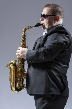 Music Ideas and Concepts. Portrait of Mature Caucasian Portrait of Mature Caucasian  Saxophone Player in Sunglasses Playing the Saxophone in Studio Environment Saxophon