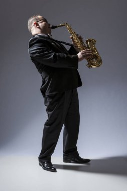Full Length Portrait of Mature Expressive Caucasian Saxophone Player in Sunglasses Playing the Saxophone in Studio