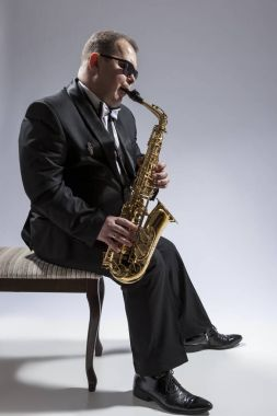 Portrait of Mature Relaxed and Thoughtful Caucasian Saxophone Player in Sunglasses Playing the Saxophone