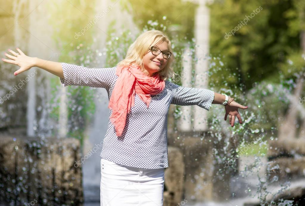 Mature Middle Aged Smiling Blond Woman Wearing Spectacles Posing Outdoors in Park