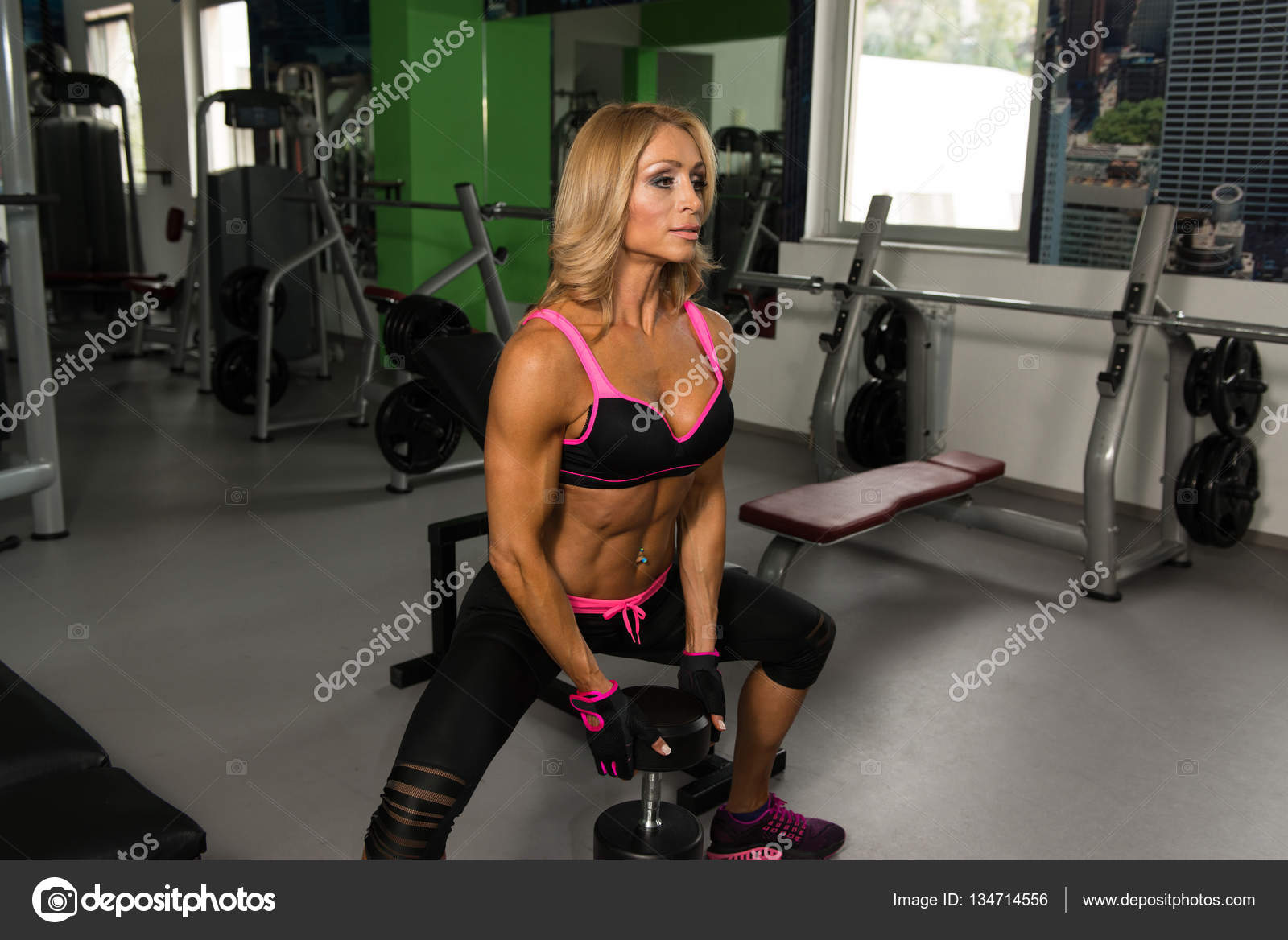 mature woman doing butt exercise with dumbbells — stock photo